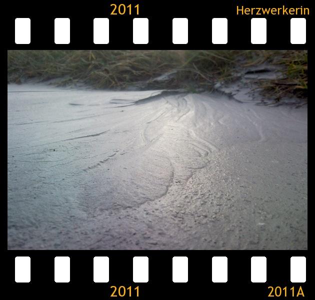 Angeschwemmter Sand in dem sich Sonne spiegelt