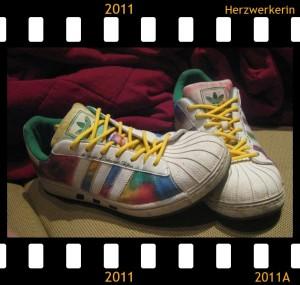 Ein Schuhpaar, ursprünglich weiß, mit ganz bunten Farben bemalt und gelben Schnürrsenkeln